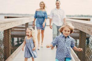 Ung familie der går på en badebro ved havet